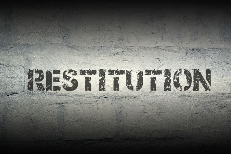 What is the difference between a fine and restitution in a criminal case?